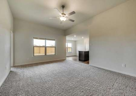 Large family room with soaring ceilings, a ceiling fan and quick access to the kitchen.