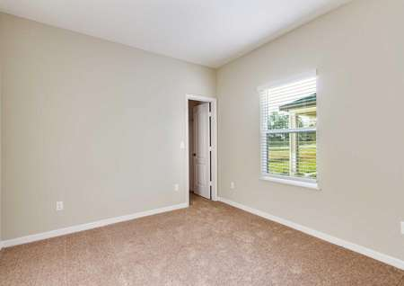 The Mykka floor plan's secondary bedroom with light brown carpet, white baseboards, tan walls and a closet.