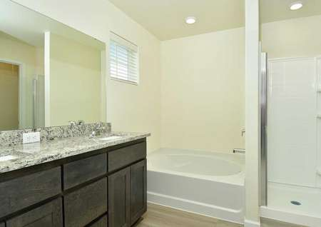 Hawthorn bathroom with dual sink vanity, brown cabinets, and white fixtures