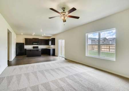 Roosevelt great room with brown ceiling fan, tan carpets, and large backyard facing window