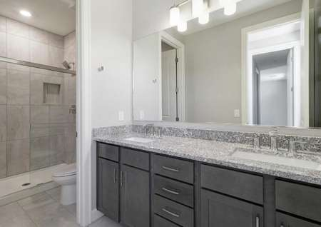 Powell master bathroom with dual sink vanities, private toilet area, and granite counters