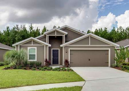 Front exterior view of the Hillcrest floor plan with a decorative garage and a lush green grass front yard.