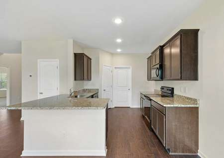 Angle of the Cypress model's kitchen showing the granite countertops, black appliances, dark brown crown moldedcabinetry with recessed lighting, and wood style vinyl flooring