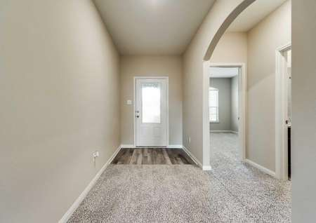 Front entryway with tan walls, white trim and a three-quarter lite front door.