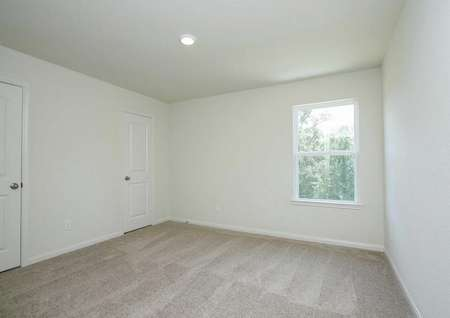 Bedroom in the Mesquite home with brown carpet flooring, white walls, white baseboards, and a window. The bedroom's door is in the back-left corner