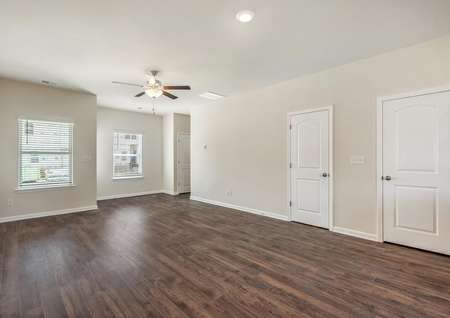 The spacious family room has wood-style flooring, great natural light and a ceiling fan.