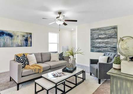 The fully furnished living room in the Walnut floor plan that has a ceiling fan, white walls and light-brown carpet flooring