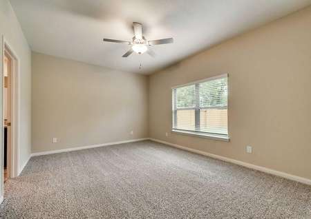 Tahoe bedroom with ceiling fan, off white walls and brown carpets