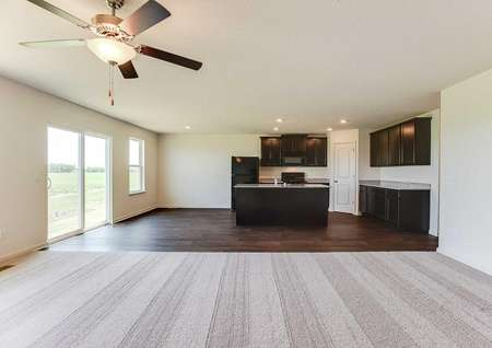 Hennepin great room finished with overhead ceiling fan, brown carpeting, and brown cabinets in the kitchen