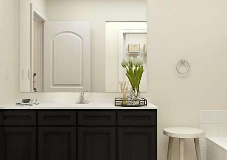 Rendering of the Maple master bath focused on the vanity with dark brown cabinets and decorated with a tray holding flowers and a scent diffuser.