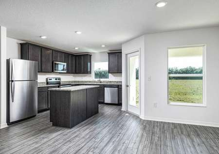 Large windows from covered back patio letting in natural light to the home's family room and chef-ready kitchen.