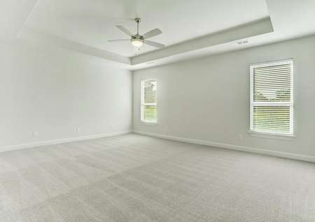 The master suite has light carpet, white walls and a ceiling fan.