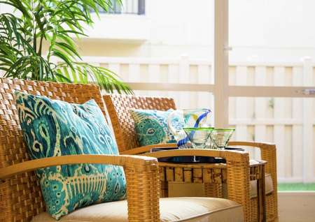 Sea Forest Beach Club model home completed with wooden chairs that have turquoise pattern pillows and beige cushions, table with glasses sitting on it, and a house plants in the background