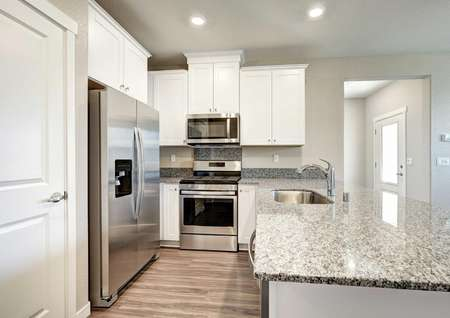 The Empire floor plan kitchen with wood-like flooring, stainless steel appliances and a pantry.