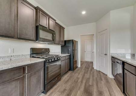Cypress kitchen with granite counters, can lights, and modern black appliances