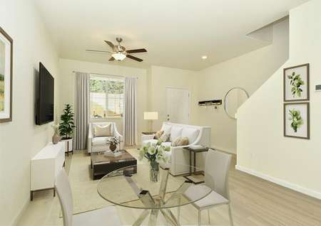 staged entertaining area, glass table with 2 chairs, sofa, armchair, coffee table, rug, tv on wall, fan, art, mirror in entry