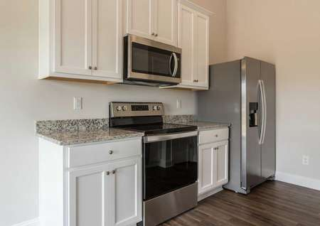 Alexander kitchen with white cabinets, granite counters, and modern appliances