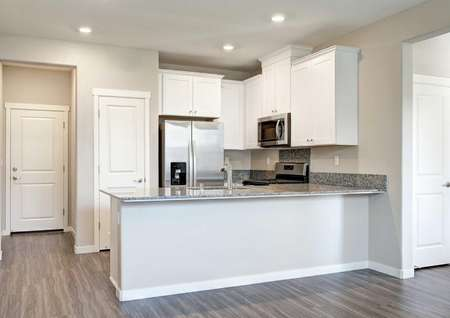 The kitchen in the Empire floor plan with vinyl wood flooring, granite countertops and a breakfast bar.