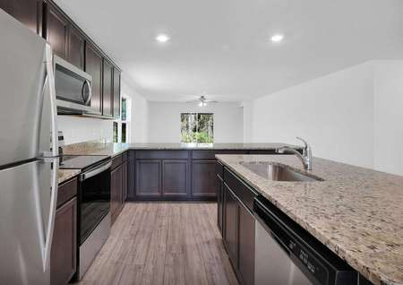 Kitchen angle view of stainless steel appliances and the family room.