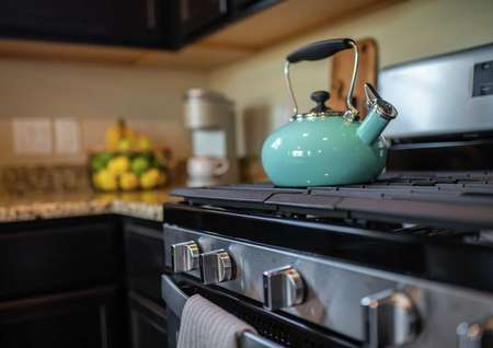Model home kitchen completed with stainless steel modern stove with a turquoise color antique teapot sitting on top of it