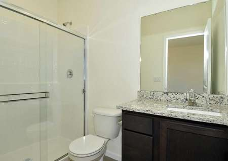 Aspen bathroom with granite counter, white toilet, and brown cabinet