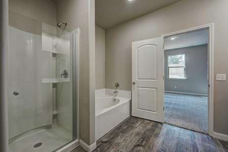 Sabine master bathroom with separate shower and bathtub, white door, and wood floors