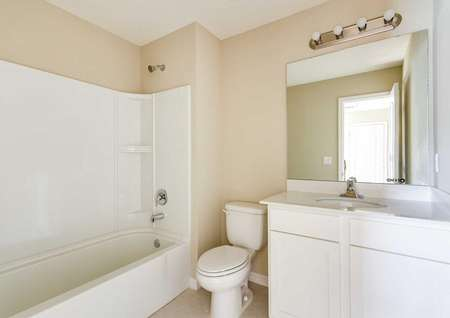 The Wekiva floor plans bathroom has a bathtub/shower combo, a toilet, white cabinetry and quartz countertops.