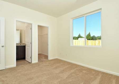 Aspen master bedroom with large window, private bathroom, and soft carpeted floors