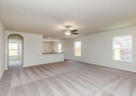 Pecan family room with light color carpet, large white framed windows, and overhead fan