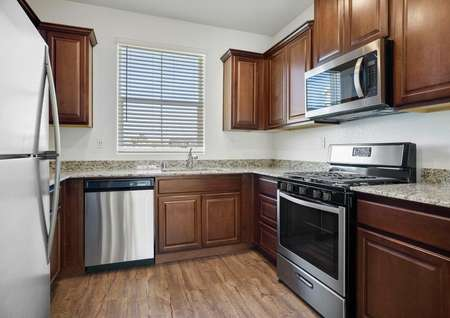 Chef-ready kitchen with stainless steel appliances, wood cabinets and granite countertops.