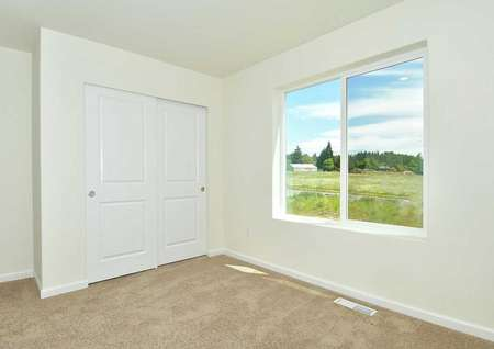 Hawthorn bedroom with large white frame window, sliding white closet doors, and brown carpet