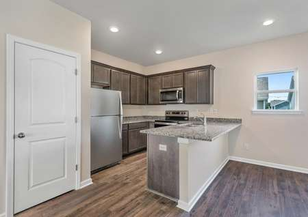 The kitchen has sprawling granite countertops, brown cabinetry and a full suite of stainless steel appliances.