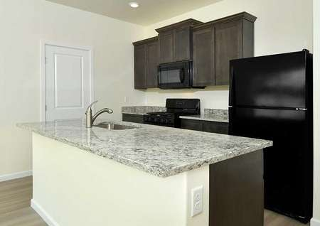 Hawthorn kitchen with granite countertops, black appliances, and brown cabinetry
