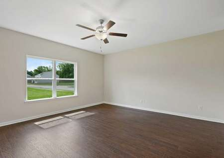 Another view of the living room in the Cypress home with wood style vinyl flooring, ceiling fan, andlarge window