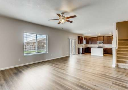 San Juan great room with wood floors, carpeted stairs, and ceiling fan