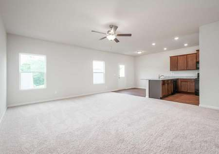 Charleston family room with attached kitchen, light color carpet, and ceiling fan