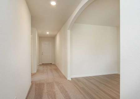 Trinity hallway with brown carpeting, recessed lights, and white on white walls