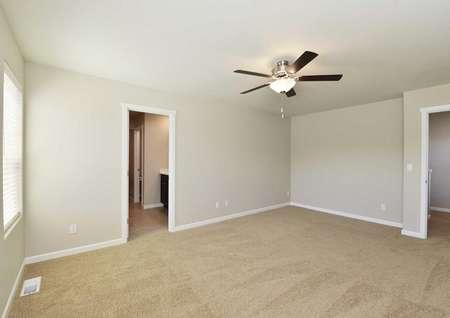 Larch bedroom with ceiling fan, light brown carpet, and white trimmed walls