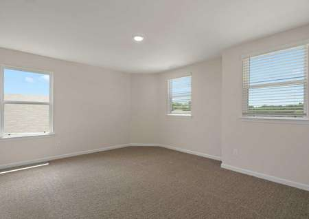 A Driftwood planbedroom with tan carpet flooring, white baseboards, three large windows throughout the room
