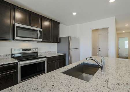 A stunning, chef-ready kitchen with stainless appliances, granite countertops and flush mount lighting.
