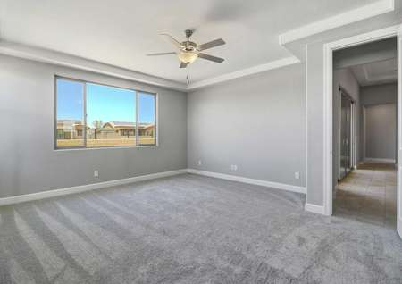 Powell bedroom with light grey carpet, white on grey walls, and ceiling fan/light fixture