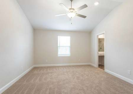 Avery master bed with vaulted ceilings, fan, and brown carpets