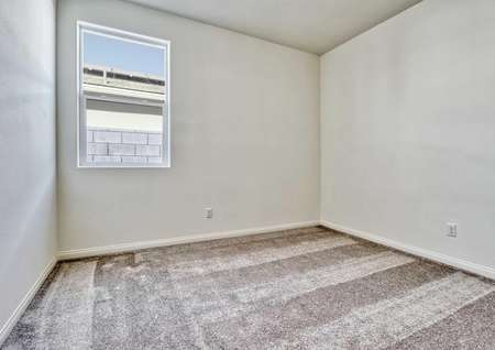 A bedroom in the Rosebud floor plan with white walls, white baseboards and light brown carpet flooring.
