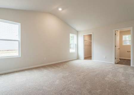 Master bedroom with two large windows, recessed lighting and carpet.
