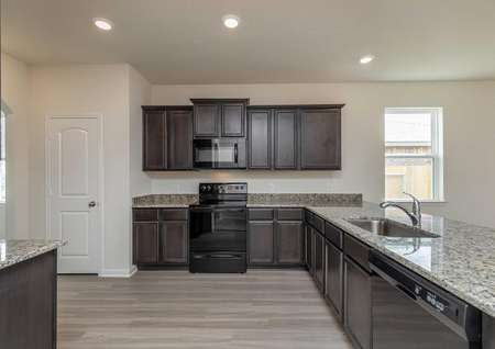 Maple kitchen with recessed light, black stove and microwave, and undermount sink on granite counters