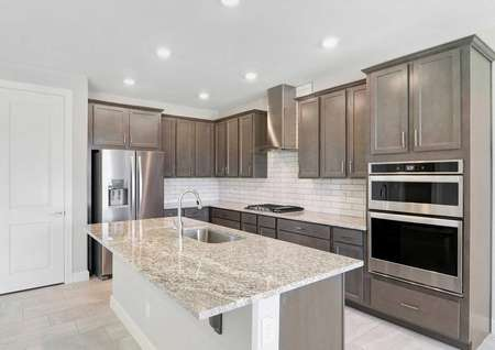 Bartlett kitchen with modern stainless steel appliances and hood, granite countertops, and large food prep island with sink