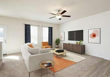 Spacious living room with beige carpet, ceiling fan and two windows decorated with white modern sofa, orange and beige rug, orange side chair, modern TV cabinet with large TV mounted on wall, round side table and industrial coffee table.