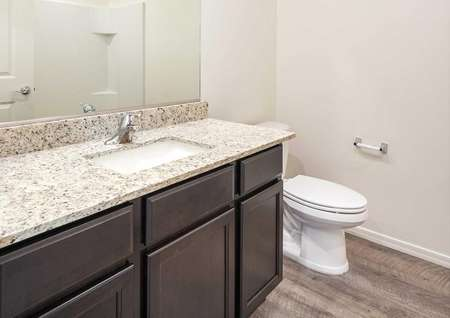 The Crescent floor plan second bathroom shown with a granite sink countertop and dark brown cabinets.