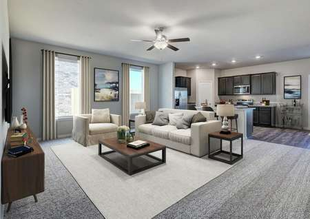 Staged living room with tan couch open to the kitchen with brown cabinets and stainless steel appliances.