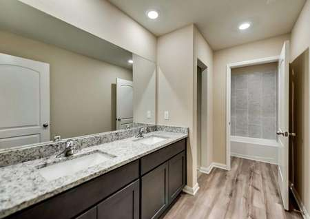 Secondary bath with double-sink vanity, brown cabinetry and vinyl floors.